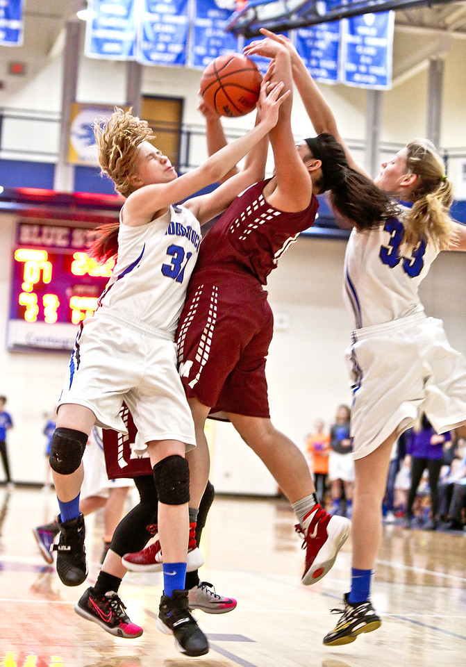 Michelle LaVigne/ For Shaw Media Woodstock's Emma Bran and Diana Spokas attempt to gain the rebound from Marengo's Trinity Chanthalansy during Thursday's game at Woodstock High School on February 9th, 2017.