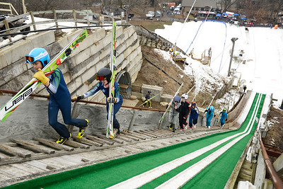 Ski jumpers competing in the U14 and U16 divisions walk up the 45 meter track to complete practice runs before the completion. Seventeen athletes competed in these two divisions.