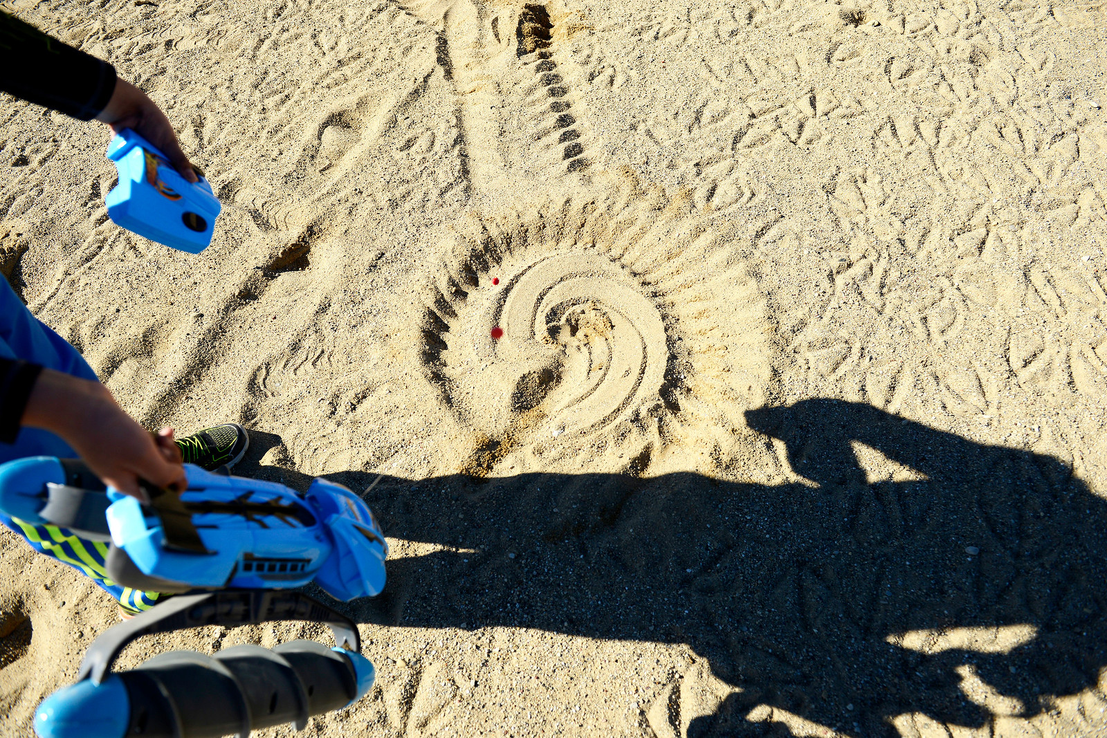 Kayla Wolf for Shaw Media–Ranveer Dhingra, 7, points out a design in the sand that the remote control toy he was playing with made Saturday, Feb. 18, 2017, at Three Oaks Recreation Area in Crystal Lake. Dhingra's family was having a picnic at the park.