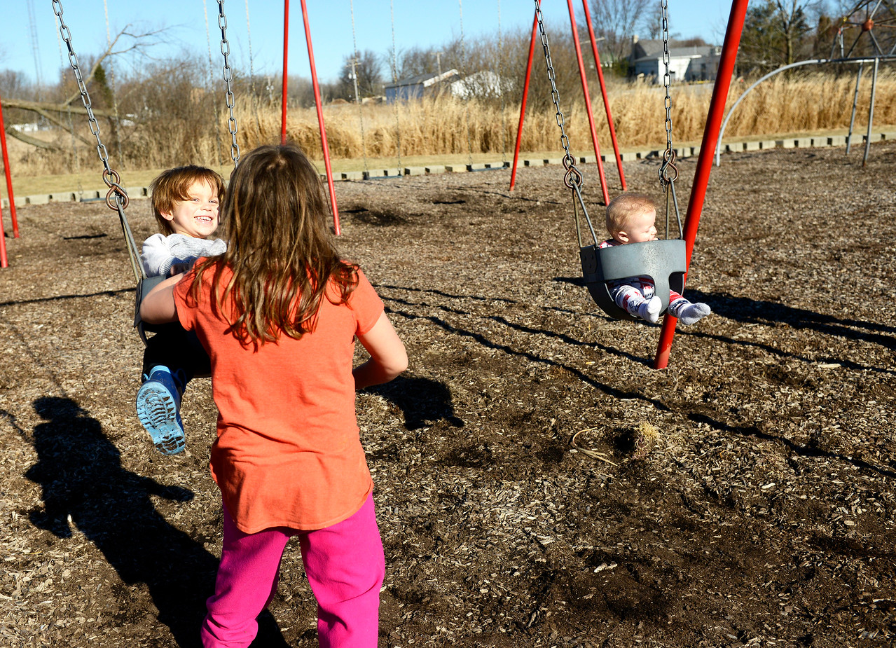 Kayla Wolf for Shaw Media– Older sister Ava Ruble pushes her brother Jest, far left, on the swings Saturday, Feb. 18, 2017, as their youngest brother Nicholas is pushed by mother Nicole, not pictured. The family made a trip to Waitcus Park in Gilberts because the weather was nice.