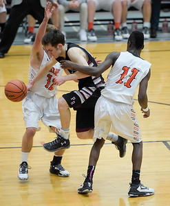 Prairie Ridge junior Connor Kazin drives to the baskets, but is blocked by McHenry Warriors James Mulhall, left, and Maki Mohr. The Warriors won 53 to 51.