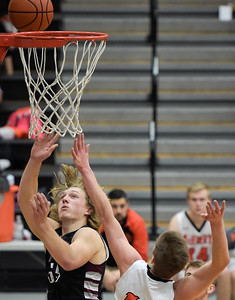 Prairie Ridge senior Austen Ferbet (cq) makes a layup as McHenry sophomore Brian March attempts to block the shot during a conference game at McHenry High School on Friday, February 3, 2017.