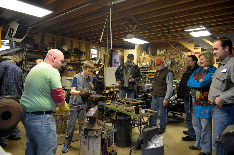 Members of the Anvil and Hammer blacksmithing club watch as Kevin Tebo, front left, and Nick Militello, 12, work on a project Saturday, Feb. 4, 2017.