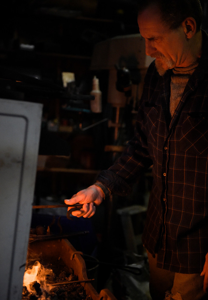 Jeff Freund places iron into the forge while working on making a decorative hook at the monthly meeting of Anvil and Hammer blacksmithing club in McHenry on Saturday, Feb. 4, 2017.