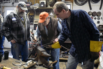 Jerry Freund the founder of Anvil and Hammer blacksmithing club shows his sons Bryan, left, and Jeff how to make an iron rod into a flat, tapered, point Saturday, Feb. 4, 2017. Jerry started the club in August 2016.