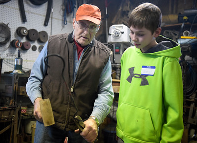 Jerry Freund  explains to Nick Militello, 12, how he made decorative twists on an S hook he was working on during an Anvil and Hammer blacksmithing club Saturday, Feb. 4, 2017. Freund was using a wooden hammer and a wood block on the anvil to pound the iron straight without harming the decorative twist that were already forged in the iron.