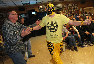 Candace H. Johnson-For Shaw Media John Schryver, of Woodstock greets wrestler, Huevos de Oros, as he makes his entrance during POWW Entertainment's Live Pro Wrestling at the American Legion in Fox Lake.