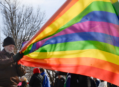 Bill Twigg unfurls a rainbow flag during a rally at McCormick Park on Sunday, Feb. 5.