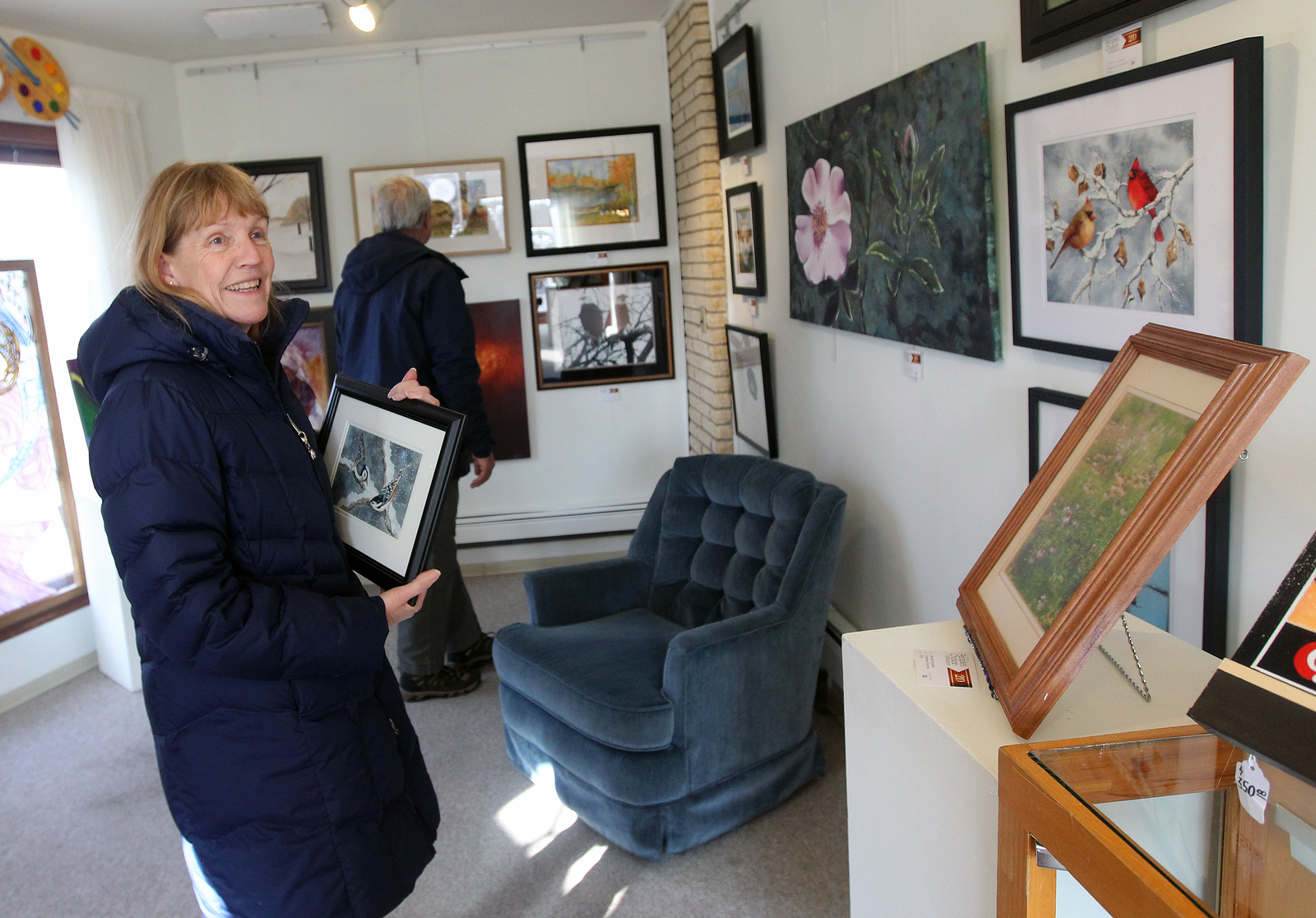 Candace H. Johnson-For Shaw Media Betsy and George Schau, of Kenosha, Wis., look at the artwork entered in the People's Choice Exhibition at the Antioch Fine Arts Foundation Art Gallery & Education Center on Route 83 in Antioch. Betsy was holding a piece of artwork by Pat King, of Waukegan, a watercolor titled, Nuthatches, she bought at the gallery.