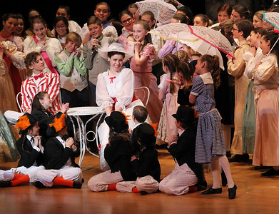 "Candace H. Johnson-For Shaw Media Anna Brown, 17, of Fox Lake (center) as Mary Poppins  listens to the cast sing, ""Jolly Holiday,"" in Act I during Spotlight Youth Theater's Mary Poppins at the College of Lake County in Grayslake."