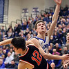 Geneva's Matt Johnston puts up a shot after plowing into St. Charles East's Nathan Ortiz during a game in Geneva on Feb. 10. The Vikings won 74-56.