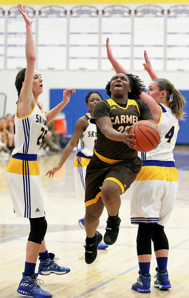 Candace H. Johnson-For Shaw Media Carmel's Ranya Jamison finds an opening against Kayla Stefka and Megan Madsen in the first quarter during the Class 3A sectional semifinal game at Johnsburg High School.