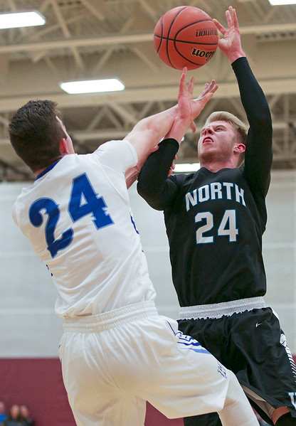 Collin Mergl (24) from Woodstock North is fouled by Josh Turner (24) from Woodstock during the first quarter of their Class 3A regional game at Richmond-Burton High School on Monday, February 27, 2017 in Richmond. The Blue Streaks defeated the Thunder 56-44. John Konstantaras photo for the Northwest Herald