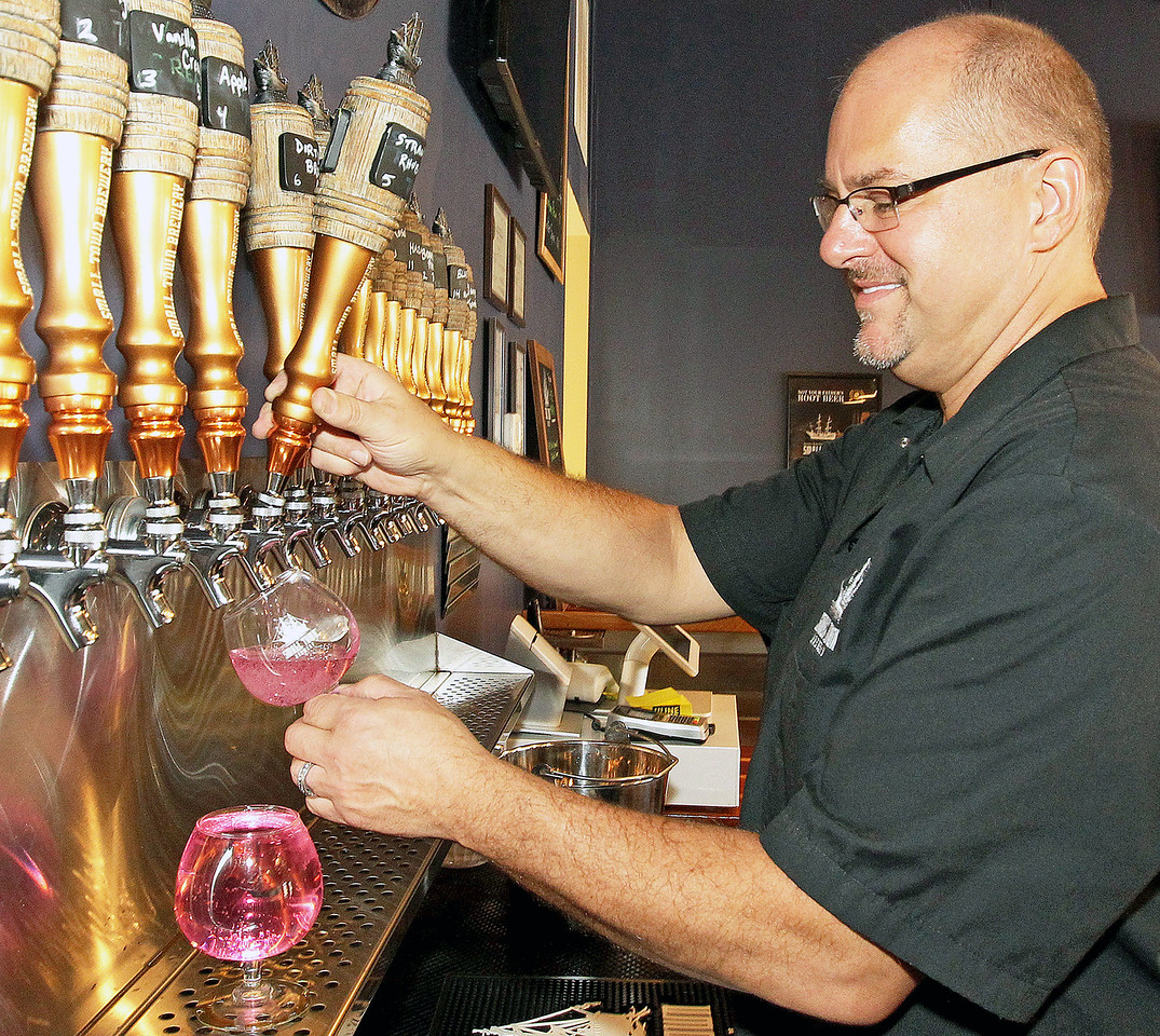 Candace H. Johnson-For Shaw Media Brewmaster Tim Kovac pours a glass of Not Your Mom's Strawberry Rhubarb beer in the Tap Room at the Small Town Brewery in Wauconda.