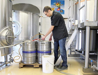 Candace H. Johnson-For Shaw Media Kenny Ludvigsen, assistant brewer, fills up kegs with Blueberry Kombucha beer at the Small Town Brewery in Wauconda.