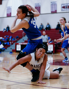 Nichole Piquette (35) from Woodstock trips over Trinity Chanthalansy (11) from Marengo during the fourth quarter of their game at Marengo High School on Thursday, February 8, 2018 in Marengo, Illinois. The Indians defeated the Blue Streaks 70-43. John Konstantaras photo for Shaw Media