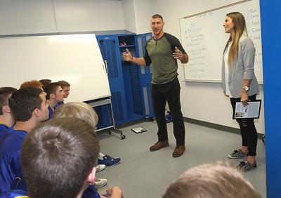 Candace H. Johnson-For Shaw Media C.J. Fiedorowicz and his sister, Paige, give a pep talk to the varsity boys basketball players before their game against Richmond-Burton after they both were inducted into the Athletic Hall of Fame at Johnsburg High School.