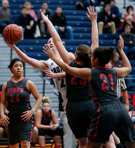 Katie Sowa (21) from Cary-Grove leans past Megan McClure (23) and Erika Burns (21) from South Elgin to put up a shot in the first quarter of their Class 4A South Elgin Regional game on Tuesday, February 13, 2018 in South Elgin, Illinois. The Trojans defeated the Storm 69-37. John Konstantaras photo for Shaw Media