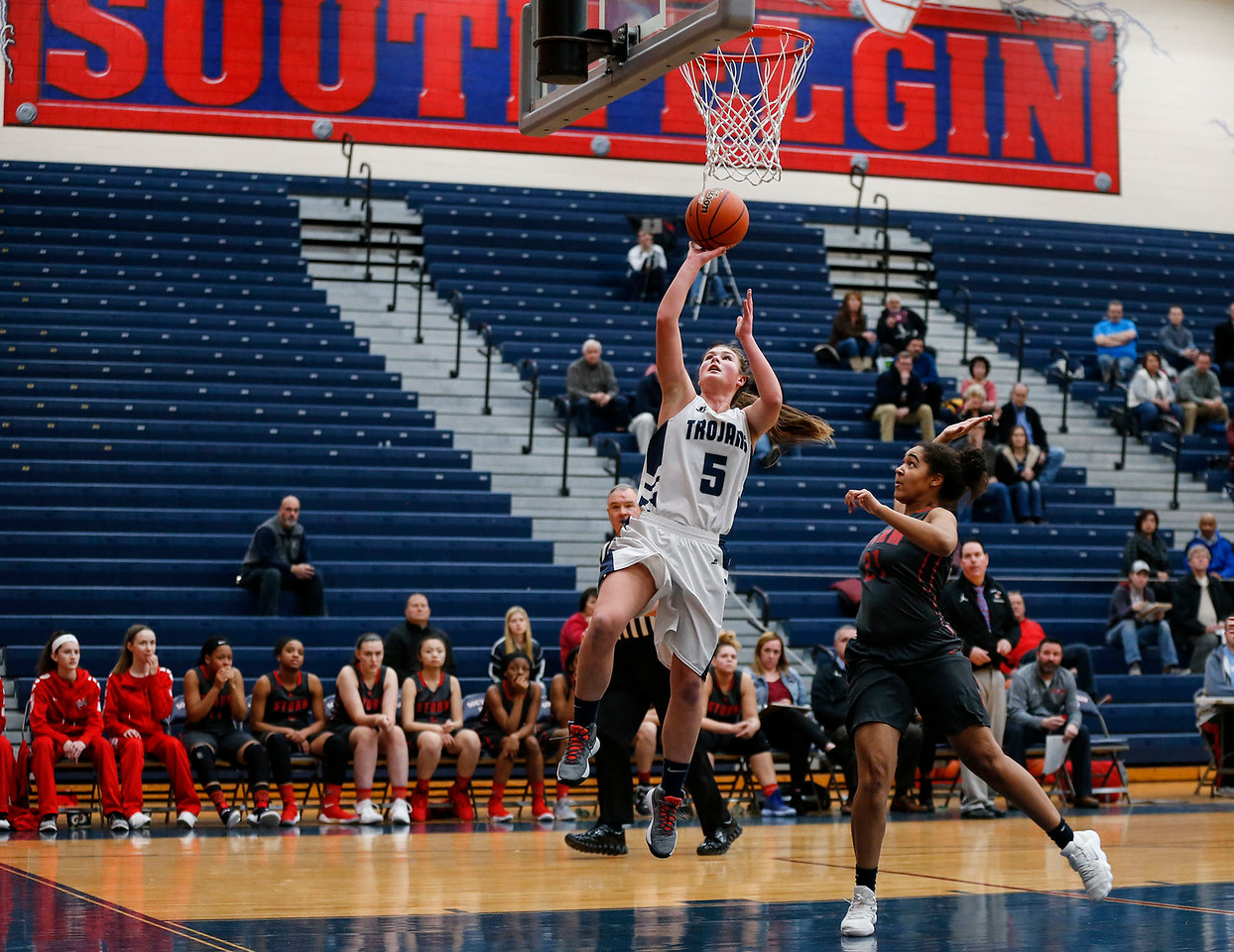 Maddie Jannusch (5) from Cary-Grove drives in for a layup over Erika Burns (21) from South Elgin in the second quarter of their Class 4A South Elgin Regional game on Tuesday, February 13, 2018 in South Elgin, Illinois. The Trojans defeated the Storm 69-37. John Konstantaras photo for Shaw Media