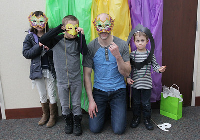 Candace H. Johnson-For Shaw Media Nathan Parker, of Lake Villa (second from the right) poses for a picture with his children, Maya, 9, Bennett, 7, and Asher, 4, as they hold up different masks during the Mardi Gras Celebration at the Lake Villa District Library.(2/10/18)