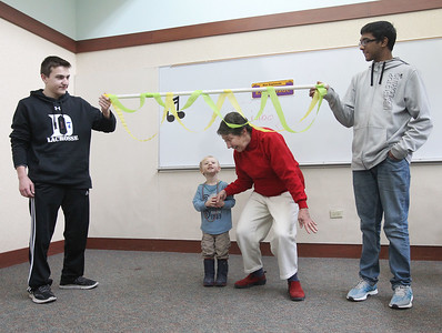 Candace H. Johnson-For Shaw Media Volunteers Dylan Mount, 14, and Anish Naik, 16, hold the Limbo pole as Nicholas Echweira, 2, and his grandmother, Michele Welch, all of Lindenhurst, go under it during the Mardi Gras Celebration at the Lake Villa District Library.(2/10/18)