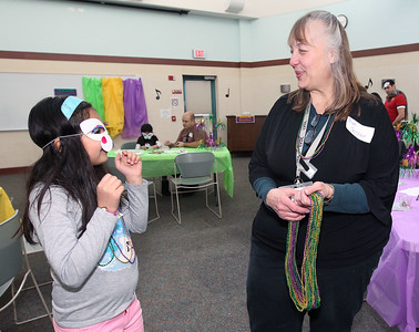 Candace H. Johnson-For Shaw Media Misela Ramirez, 7, of Waukegan shows Cathy Cheesbrough-Gola, youth services associate, the mask she made during the Mardi Gras Celebration at the Lake Villa District Library.(2/10/18)