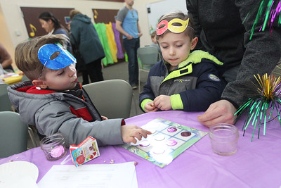 Candace H. Johnson-For Shaw Media Dylan Aldrich, 4, of Lindenhurst plays Mardi Gras Tic-Tac-Toe with his brother, Clayton, 5, during the Mardi Gras Celebration at the Lake Villa District Library.The boys were at the event with their father, Tim, who stood beside Clayton.(2/10/18)