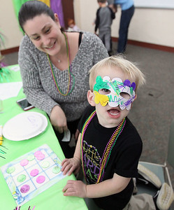 Candace H. Johnson-For Shaw Media Heather Ronney, of Lake Villa watches her son, Colin, 2, show off his Mardi Gras mask that he made during the Mardi Gras Celebration at the Lake Villa District Library.(2/10/18)