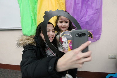 Candace H. Johnson-For Shaw Media Ileana Rojas, of Lake Villa takes a selfie with her daughter, Oriana, 5, as she holds a frame during the Mardi Gras Celebration at the Lake Villa District Library.(2/10/18)