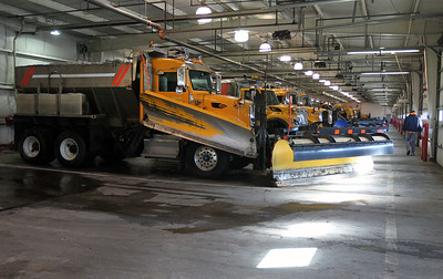 Candace H. Johnson-For Shaw Media A plow operator walks beside a line of plow trucks used to clear the snow and ice off of Lake County streets at the Lake County Division of Transportation on Winchester Road in Libertyville.Twenty-six plow trucks and three spare trucks sit in the truck barn.(2/12/18)