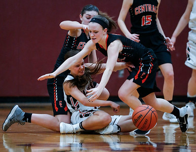 Ashley Wachter (10) from McHenry scrambles to pass a ball between Corrine Hamill (3, left) and Elise Olson (5) from Crystal Lake Central in the second quarter during their IHSA Class 4A girls basketball regional championship game on Thursday, February 15, 2018, in Crystal Lake, Illinois.  The Warriors defeated the Tigers. John Konstantaras photo for Shaw Media