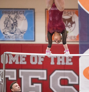 Whitney Rupp for Shaw Media  Kira Karlblom performs on the uneven bars at the IHSA State Championships in Palatine Saturday, Feb. 17 as head coach Lee Battaglia watches.