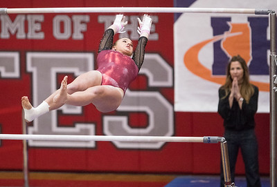 Whitney Rupp for Shaw Media  Kira Karlblom performs on the uneven bars at the IHSA State Championships in Palatine Saturday, Feb. 17 as assistant coach Lisa Rumford looks on.