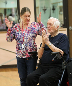 Candace H. Johnson-For Shaw Media Instructor Carol Kiraly, works with Chuck McCann, of Round Lake Beach on starting with a prayer position and then opening up his hands to reach up and breathe during Yoga for Seniors at the Robert W. Rolek Community Center in Round Lake.(2/20/18)