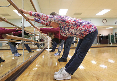 Candace H. Johnson-For Shaw Media Instructor Carol Kiraly, of McHenry works with her class to stretch as they hold on to a bar during Yoga for Seniors at the Robert W. Rolek Community Center in Round Lake.(2/20/18)