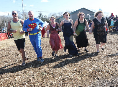Candace H. Johnson-For Shaw Media Mike Conley, Steve Hermanson, his wife, Kristine, Cory Knopik, Christy Hardin and Judy Rausch, all with the Woodstock Community Unit School District 200 team, head for the water during the Polar Plunge at Lakefront Park in Fox Lake.