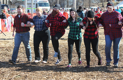 Candace H. Johnson-For Shaw Media Plungers with the Lumberjack team from the Creekside Middle School in Woodstock go arm-in-arm towards the water during the Polar Plunge at Lakefront Park in Fox Lake.