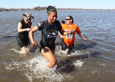 Candace H. Johnson-For Shaw Media Ishta Nabakka, 16, of McHenry (center) with the McHenry West Plungers gets ahead of the others as she makes her way out of Nippersink Lake during the Polar Plunge at Lakefront Park in Fox Lake.