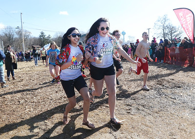 Candace H. Johnson-For Shaw Media Grant freshmen Priya Audipudy, of Round Lake and Hannah Newport, of Lakemoor, both 14, run into the water during the Polar Plunge at Lakefront Park in Fox Lake.(2/25/18)