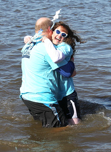 Candace H. Johnson-For Shaw Media James Williams, of Lake in the Hills, Special Olympics global messenger, gives a hug to Sgt. Amy Williams with the Huntley Police Dept. as they make their way through Nippersink Lake during the Polar Plunge at Lakefront Park in Fox Lake. Proceeds from the event will benefit the athletes of Special Olympics Illinois.