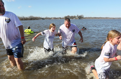 Candace H. Johnson-For Shaw Media Alexandra Roske, 12, and her father, Bob, a McHenry police officer, make their way out of frigid Nippersink Lake with the McHenry Police Department team during the Polar Plunge at Lakefront Park in Fox Lake.