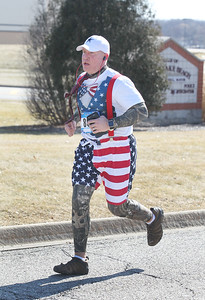 Candace H. Johnson-For Shaw Media Matt Boren, of Round Lake Beach runs past the Village Hall as he makes his way to the finish line on Municipal Way during the Frosty Footrace 5K Run/Walk at the Round Lake Area Park District Sports Center in Round Lake Beach. Boren's wife, Amy, son, Alex, and their dog, Bacon, were also at the event.(2/25/18)