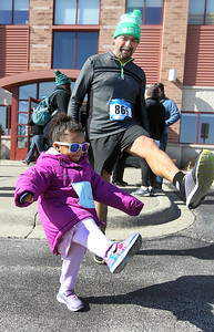 Candace H. Johnson-For Shaw Media Cataleya Ortiz, 2, of Round Lake stretches with her grandfather, Alberto Cardenas, of Round Lake Beach, before he races in the Frosty Footrace 5K Run/Walk at the Round Lake Area Park District Sports Center in Round Lake Beach. Cardenas ran with his daughter, Rosanna Ortiz, and both were training for the Chicago Marathon.(2/25/18)