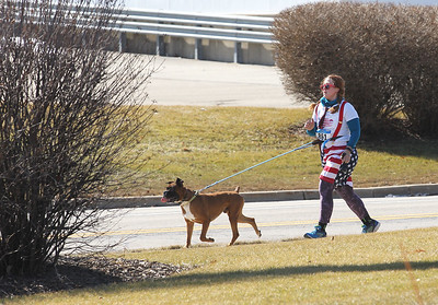 Candace H. Johnson-For Shaw Media Amy Boren, of Round Lake Beach runs with her Boxer named, Bacon, on Hook Drive during the Frosty Footrace 5K Run/Walk at the Round Lake Area Park District Sports Center in Round Lake Beach. Boren was at the event with her husband, Matt, and son, Alex.(2/25/18)