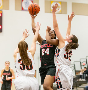 Huntley's Kamsi Nwogu goes up for a shot over McHenry defenders Megan Cooper (Left) and  Katie Beyer Monday, February 4, 2019 in McHenry. McHenry went on to win the game 36-25. KKoontz – For Shaw Media