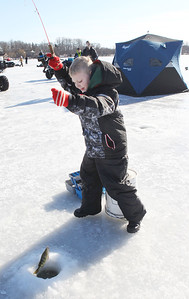 Candace H. Johnson-For Shaw Media Brodie Tillert, 8, of Ingleside catches a perch during the 59th Annual Chain O' Lakes Ice Fishing Derby and Winter Festival at Turtle Beach on Channel Lake in Antioch. The event was sponsored by the Northern Illinois Conservation Club. Brodie was at the event with his mother, Sandy, and it was his first time ice fishing.(2/9/19)