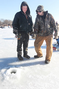 Candace H. Johnson-For Shaw Media Ava Sunich gets some help ice fishing from her boyfriend, Derek Dschida, both of Antioch during the 59th Annual Chain O' Lakes Ice Fishing Derby and Winter Festival at Turtle Beach on Channel Lake in Antioch. The event was sponsored by the Northern Illinois Conservation Club. This was Sunich's first time ice fishing.(2/9/19)