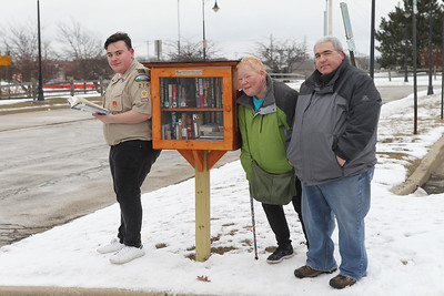 Candace H. Johnson-For Shaw Media Dante Rivera, 17, of Round Lake with Boy Scout Troop 275 stands with his parents, Ilene and Luis, next to the Little Free Library he made for his Eagle Scout project, located at the Round Lake Beach Metra train station. (2/16/19)