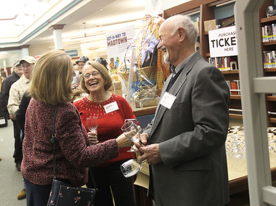 Candace H. Johnson-For Shaw Media Anita Dolan, of Lindenhurst shares a laugh with Jeanne Gundrum, of Lake Villa and her husband, Tony, as they pass out wine glasses during Grapes & Growlers-A Night at the Library at the Lake Villa District Library. Grapes & Growlers is the Lake Villa District Foundation's annual winter event with wine and craft beer tastings. (2/15/19)