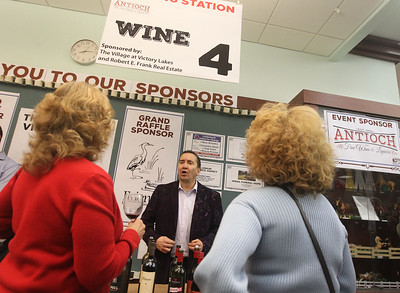 Candace H. Johnson-For Shaw Media Joe Gepperth, of Huntley talks to Carol Esler and Yvonne Hustak, both of Gurnee after serving them wine during Grapes & Growlers-A Night at the Library at the Lake Villa District Library. Grapes & Growlers is the Lake Villa District Foundation's annual winter event with wine and craft beer tastings. (2/15/19)